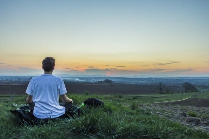 парень медитирует на холме