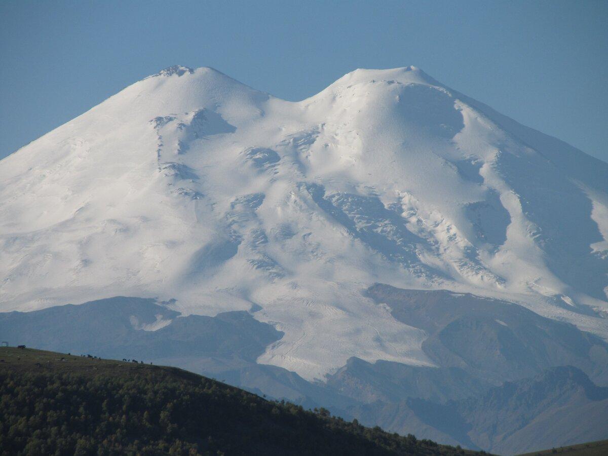 На фотографии хорошо видна мощность одного из ледников Эльбруса и кратеры на его вершинах